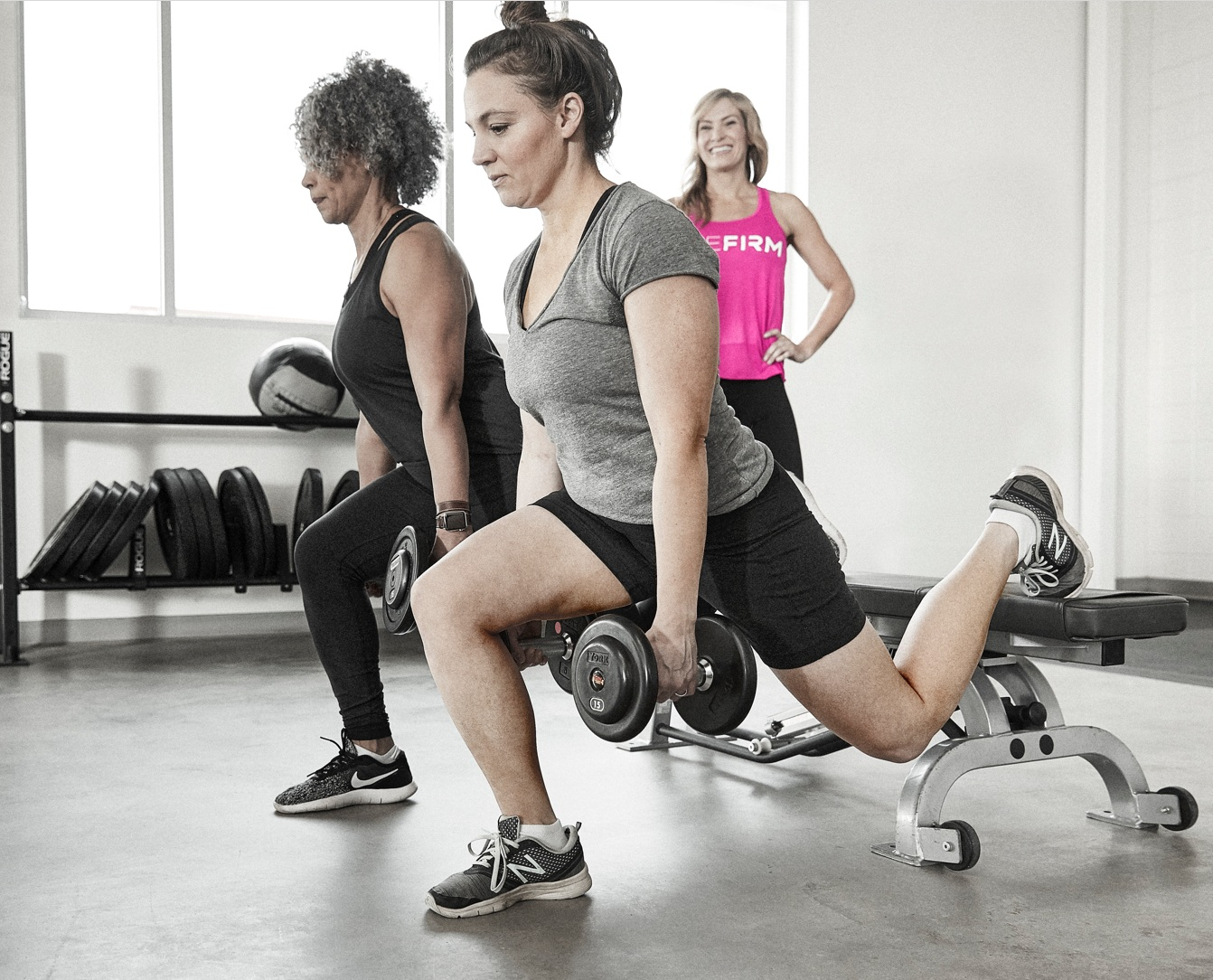 Two women work out using The Firm's state-of-the-art equipment